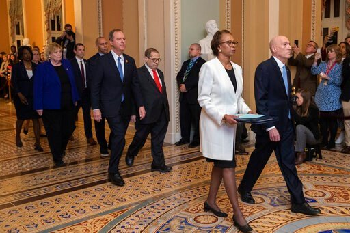 (AP Photo/Manuel Balce Ceneta). House Sergeant at Arms Paul Irving and Clerk of the House Cheryl Johnson carry the articles of impeachment against President Donald Trump to Secretary of the Senate Julie Adams on Capitol Hill in Washington, Wednesday, J...