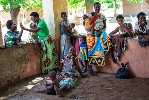 (AP Photo/Jerome Delay). In this photo taken Wednesday, Dec. 11, 2019, residents of the Malawi village of Tomali wait to have their young children become test subjects for the world's first vaccine against malaria. Babies in three African nations are g...