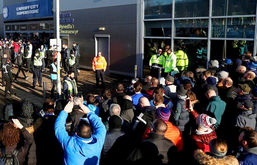 (David Davies/PA via AP). FILE - In this file photo dated Sunday Jan. 12, 2020, soccer fans crowd outside the Cardiff City soccer stadium ahead of the English Championship match against Swansea City, in Cardiff, Wales, as South Wales police are schedul...