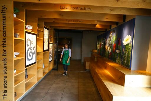 (AP Photo/Ross D. Franklin). In this Wednesday, Jan. 15, 2020, photo, Belith Ariza, a barista trainer at Starbucks, walks back to the main store from the community meeting space at a local Starbucks Community Store, in Phoenix. The Seattle-based compan...