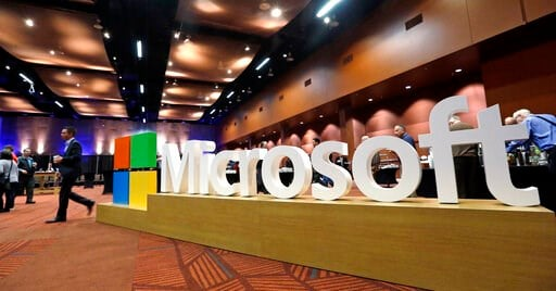 (AP Photo/Elaine Thompson, File). FILE - In this Nov. 30, 2016, file photo a man walks past a Microsoft sign at the annual Microsoft shareholders meeting in Bellevue, Wash. Microsoft on Thursday, Jan. 16, 2020, is announcing a plan to reduce its carbon...