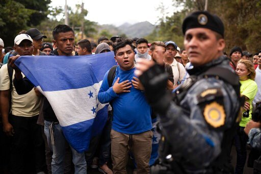 (AP Photo/Santiago Billy). Honduran migrants walking in a group stop before Guatemalan police near Agua Caliente, Guatemala, Thursday, Jan. 16, 2020, on the border with Honduras. Less-organized migrants, tighter immigration control by Guatemalan author...