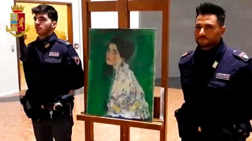 (Italian Police via AP). This image taken from a video distributed Wednesday, Dec. 11, 2019 by Italian police shows two police officers standing next to painting which was found inside a gallery's walls, in Piacenza, northern Italy. A gardener at the R...