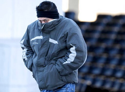 (Mike De Sisti/Milwaukee Journal-Sentinel via AP). Jorge Hernandez, of Milwaukee, tries to cover his face from the cold while walking along West Kilbourn Avenue in Milwaukee, Thursday, Jan. 16, 2020. While snow is expected Friday, breezy and cold condi...
