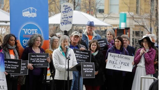 (AP Photo/Rick Bowmer). People gather outside the office of Senator Mitt Romney to call on him to push for a full and fair impeachment trial in the Senate with pertinent testimony and evidence during a rally Thursday, Jan. 16, 2020, in Salt Lake City.