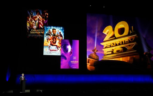 (Photo by Chris Pizzello/Invision/AP, File). FILE - In this April 3, 2019, file photo, Alan Horn, chairman of The Walt Disney Studios, speaks underneath poster images for 20th Century Fox films during the Walt Disney Studios Motion Pictures presentatio...