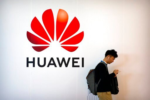 (AP Photo/Mark Schiefelbein, File). FILE - In this Oct. 31, 2019, filer photo, a man uses his smartphone as he stands near a billboard for Chinese technology firm Huawei at the PT Expo in Beijing. British and American officials are meeting as U.K. Prim...