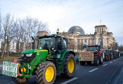 (Christophe Gateau/dpa via AP). Farmers drive past the Reichstag building with their tractors in Berlin, Saturday, Jan.18, 2020. On the occasion of the Green Week agricultural and food fair, people in Berlin demonstrate for more environmentally friendl...
