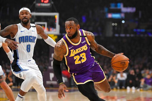(AP Photo/Mark J. Terrill). Los Angeles Lakers forward LeBron James, right, drives toward the basket as Orlando Magic guard Terrence Ross defends during the first half of an NBA basketball game Wednesday, Jan. 15, 2020, in Los Angeles.