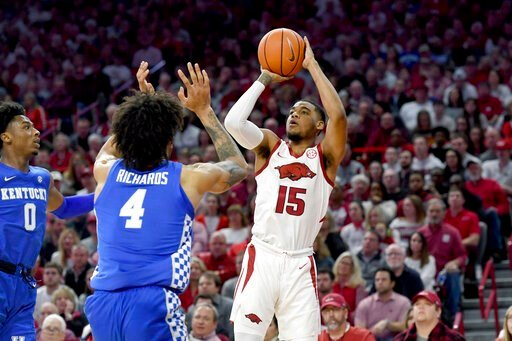 (AP Photo/Michael Woods). Arkansas guard Mason Jones (15) pulls up to shoot over Kentucky defenders Nick Richards (4) and Ashton Hagans (0) during the first half of an NCAA college basketball game, Saturday, Jan. 18, 2020, in Fayetteville, Ark.
