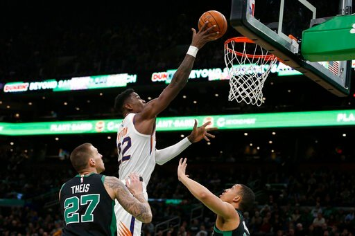 (AP Photo/Mary Schwalm). Phoenix Suns center Deandre Ayton (22) lays the ball up over Boston Celtics forward Daniel Theis (27) and forward Grant Williams (12) during the first half of an NBA basketball game, Saturday, Jan. 18, 2020, in Boston.