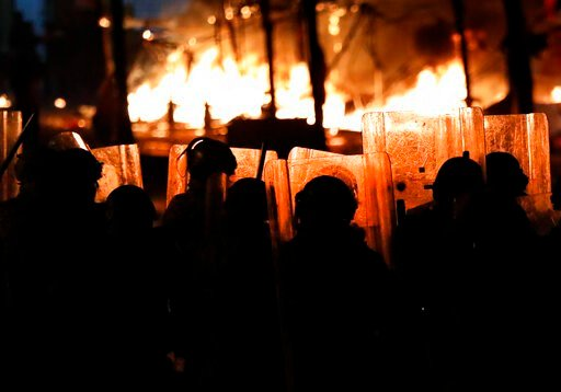 (AP Photo/Hussein Malla). Riot policemen watch flames rise from the tents of anti-government protesters, which where set on fire by civilian men believed to be the private unit of the parliament guards, during ongoing protests against the political eli...