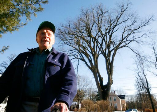 "(AP Photo/Steven Senne, File). FILE - In this Dec. 14, 2009 file photo, Frank Knight, 101, of Yarmouth, Maine, stands in front of an elm tree known as ""Herbie"" in Yarmouth. Knight took care of the tree for about 50 years while working as the Yarmouth t..."