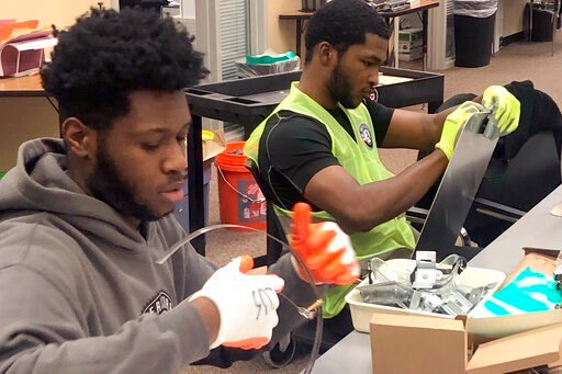 (AP Photo/Corey Williams). In this Jan. 16, 2020 photo, Nicholas Thomas, left, and Joe Wright, right, prepare school safety signs as part of the AmeriCorps Urban Safety Program at Wayne State University's Center for Urban Studies. Volunteers will post ...