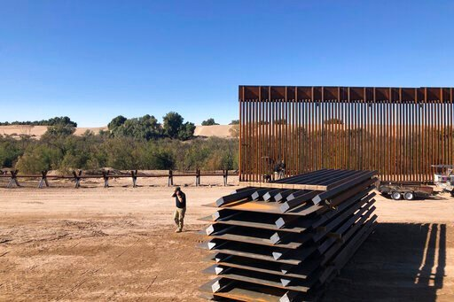 (AP Photo/Elliot Spagat). In this Jan. 10, 2020, photo, people work at a portion of border wall which is under construction in Yuma, Ariz. Illegal border crossings have plummeted as the Trump administration has extended a policy to make asylum seekers ...