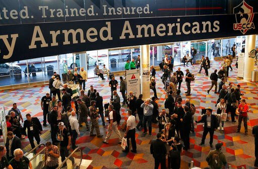 (AP Photo/John Locher, File). FILE - In this Wednesday, Jan. 24, 2018, file photo, people walk through the hall outside of the SHOT Show gun show in Las Vegas. The gun industry is gathering for its annual conference, in January 2020, amid a host of unc...
