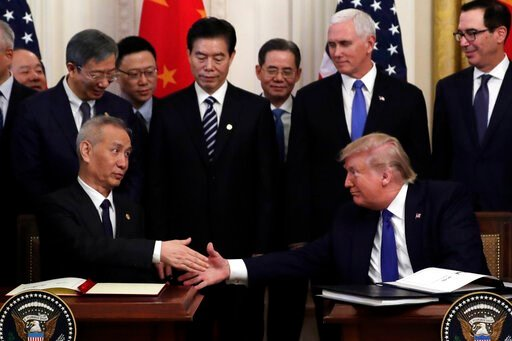 (AP Photo/Evan Vucci). President Donald Trump shakes hands with Chinese Vice Premier Liu He, after signing a trade agreement in the East Room of the White House, Wednesday, Jan. 15, 2020, in Washington.