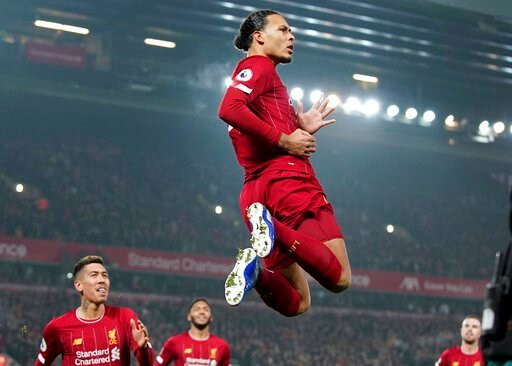 (AP Photo/Jon Super). Liverpool's Virgil van Dijk jumps to celebrate scoring his side's first goal during the English Premier League soccer match between Liverpool and Manchester United at Anfield Stadium in Liverpool, Sunday, Jan. 19, 2020.