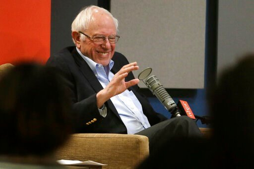 (AP Photo/Steven Senne). Democratic presidential candidate Sen. Bernie Sanders, I-Vt., smiles and waves while seated in front of an audience before the start of a forum broadcast on radio in a New Hampshire Public Radio station, Sunday, Jan. 19, 2020, ...