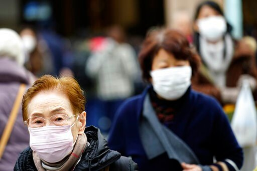 (AP Photo/Eugene Hoshiko). Pedestrians wear protective masks as they walk through a shopping district in Tokyo Thursday, Jan. 16, 2020. Japan's government said Thursday a man treated for pneumonia after returning from China has tested positive for the ...