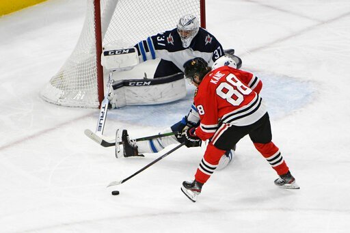 (AP Photo/David Banks). Chicago Blackhawks right wing Patrick Kane (88) skates in against Winnipeg Jets goaltender Connor Hellebuyck (37) during the first period of an NHL hockey game Sunday, Jan. 19, 2020, in Chicago.