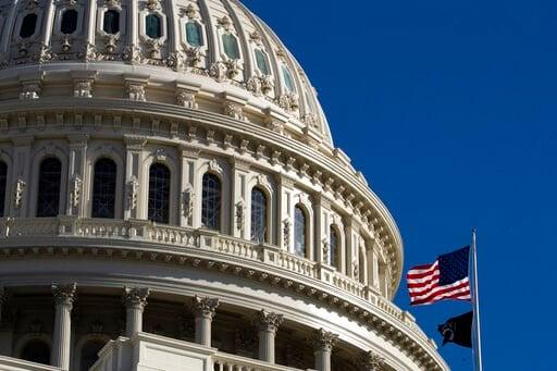 (AP Photo/Manuel Balce Ceneta). The U.S. flag flies over the U.S. Capitol in Washington, Sunday, Jan. 19, 2020.