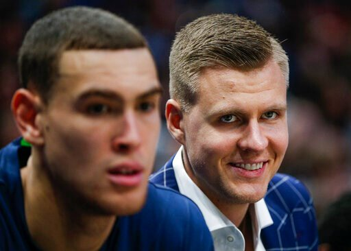 (AP Photo/Brandon Wade). Dallas Mavericks forwards Kristaps Porzingis, right, and Dwight Powell watch from the bench during the first half of the team's NBA basketball game against the Portland Trail Blazers, Friday, Jan. 17, 2020, in Dallas.