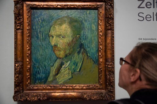 (AP Photo/Peter Dejong). A journalist takes a closer look at the previously contested painting by Dutch master Vincent van Gogh, a 1889 self-portrait, of which the authenticity was confirmed during a press conference in Amsterdam, Netherlands, Monday, ...