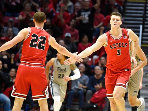 (AP Photo/Denis Poroy). San Diego State forward Yanni Wetzell (5) slaps hands with guard Malachi Flynn (22) after scoring during the second half of an NCAA college basketball game against Nevada, Saturday, Jan. 18, 2020, in San Diego.