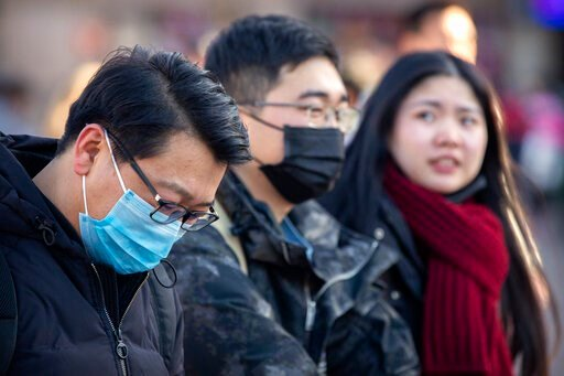 (AP Photo/Mark Schiefelbein). Travelers wear face masks as they walk outside of the Beijing Railway Station in Beijing, Monday, Jan. 20, 2020. China reported Monday a sharp rise in the number of people infected with a new coronavirus, including the fir...