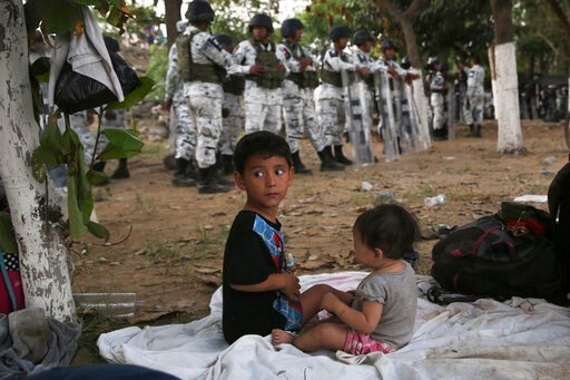 (AP Photo/Marco Ugarte). With a line of Mexican National Guardsmen behind them, a couple of migrant children campout on the Mexican shore of the Suchiate river on the border with Guatemala, near Ciudad Hidalgo, Mexico, Monday, Jan. 20, 2020. The migran...