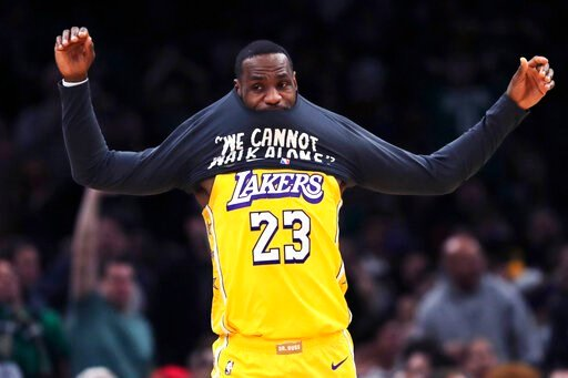 (AP Photo/Charles Krupa). Los Angeles Lakers forward LeBron James puts on a warm-up shirt as he goes to the bench during the first half of an NBA basketball game against the Boston Celtics in Boston, Monday, Jan. 20, 2020.