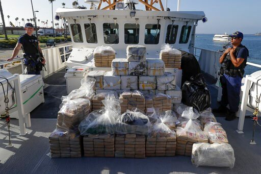 (AP Photo/Chris Carlson, file). FILE - In this Aug. 29, 2019, file photo, members of the Coast Guard stand near seized cocaine in Los Angeles. The nation's drug addiction crisis has been morphing in a deadly new direction: more Americans struggling wit...