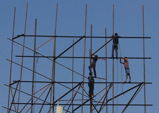 (AP Photo/Mahesh Kumar A.). Indian workers repair an advertising hoarding in Hyderabad, India, Tuesday, Jan. 21, 2020. The IMF on Monday lowered India's economic growth estimate for the current fiscal to 4.8% and listed the country's Gross Domestic Pro...