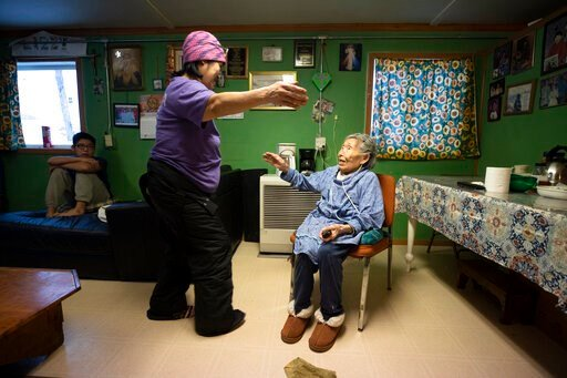 (AP Photo/Gregory Bull). In this Monday, Jan. 20, 2020 image, Lizzie Chimiugak, right, gets a hug from her granddaughter Janet Lawrence at her home in Toksook Bay, Alaska. Chimiugak, who turned 90 years old on Monday, is scheduled to be the first perso...
