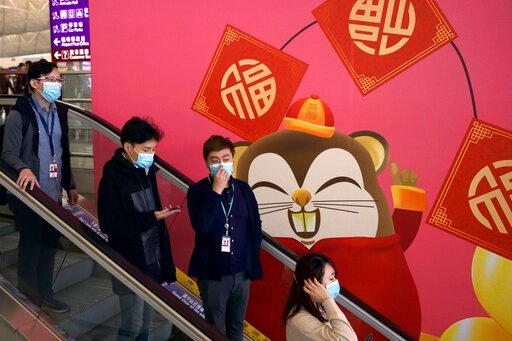 (AP Photo/Ng Han Guan). People wear face masks as they ride an escalator at the Hong Kong International Airport in Hong Kong, Tuesday, Jan. 21, 2020. Face masks sold out and temperature checks at airports and train stations became the new norm as China...