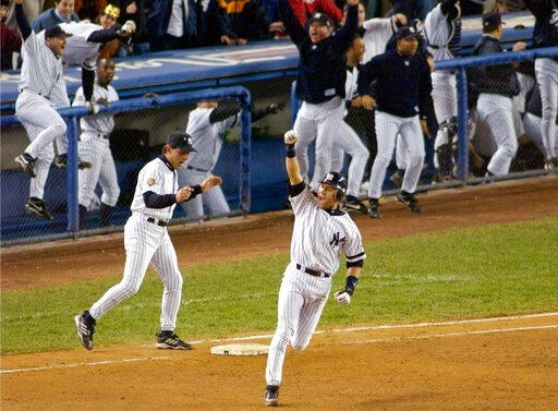 (AP Photo/Bill Kostroun, File). FIEE - In this Oct. 31, 2001, file photo, New York Yankees' Derek Jeter celebrates his game-winning home run in the 10th inning as he rounds first base in Game 4 of baseball's World Series against the Arizona Diamondback...