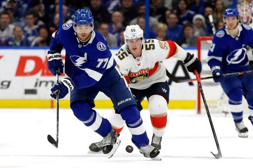 (AP Photo/Chris O'Meara). Tampa Bay Lightning defenseman Victor Hedman (77) moves the puck in front of Florida Panthers center Noel Acciari (55) during the first period of an NHL hockey game Monday, Dec. 23, 2019, in Tampa, Fla.