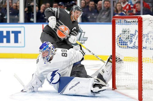 (AP Photo/Jeff Roberson). Tampa Bay Lightning goalie Andrei Vasilevskiy (88) reaches back to block a shot by Edmonton Oilers forward Connor McDavid (97) in the NHL hockey All Star final game Saturday, Jan. 25, 2020, in St. Louis.