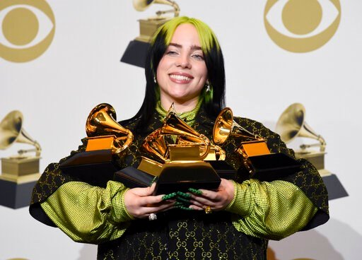 """(AP Photo/Chris Pizzello). Billie Eilish poses in the press room with the awards for best album and best pop vocal album for """"We All Fall Asleep, Where Do We Go?"""", best song and record for """"Bad Guy"""" and best new artist at the 62nd annual Grammy Awards ..."""