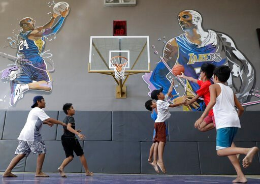 """(AP Photo/Aaron Favila). Boys plays beside images of former NBA basketball player Kobe Bryant at the """"House of Kobe"""" basketball court in Valenzuela, north of Manila, Philippines on Monday, Jan. 27, 2020. Fans left flowers and messages on the walls at t..."""