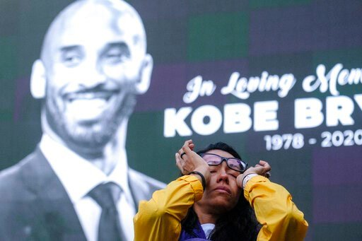(AP Photo/Ringo H.W. Chiu). Nicole Mascarenhas, wipes her eyes in front of a screen with the late Kobe Bryant at a memorial for Kobe Bryant near Staples Center Monday, Jan. 27, 2020, in Los Angeles. Bryant, the 18-time NBA All-Star who won five champio...