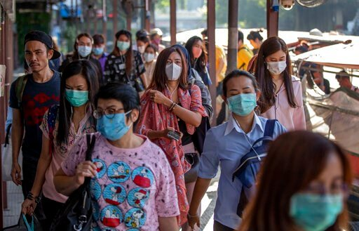 (AP Photo/Gemunu Amarasinghe). Boat passengers on a jetty wear face masks in Bangkok, Thailand, Tuesday, Jan. 28, 2020 to protect themselves from new virus infection. Panic and pollution drive the market for protective face masks, so business is boomin...