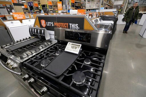 (AP Photo/Steven Senne). In this Monday, Jan. 27, 2020 photo a passer-by walks near stoves, front, at a Home Depot store location, in Boston. On Tuesday, Jan. 28, the Conference Board reports on U.S. consumer confidence for January.