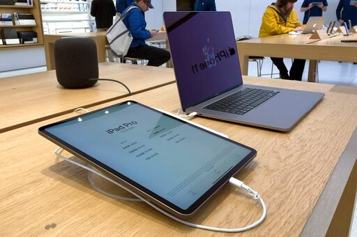 (AP Photo/Steven Senne). An iPad Pro and a Macbook Pro are displayed an Apple store Tuesday, Jan. 28, 2020, in suburban Boston. Apple reports financial earns on Tuesday.