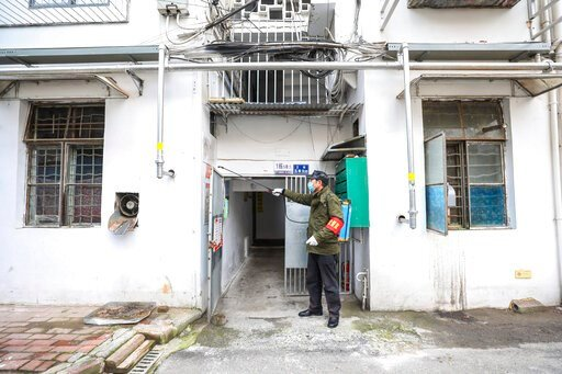 (Chinatopix via AP). A government worker sprays disinfectant on a residential building in Wuhan in central China's Hubei Province, Tuesday, Jan. 28, 2020. Hong Kong's leader announced Tuesday that all rail links to mainland China will be cut starting F...