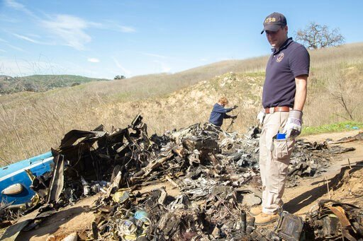 (James Anderson/National Transportation Safety Board via AP). In this image taken Monday, Jan. 27, 2020, and provided by the National Transportation Safety Board, NTSB investigators Adam Huray, right, and Carol Hogan examine wreckage as part of the NTS...