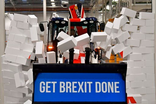 (Ben Stansall/Pool via AP). FILE - In this Tuesday Dec. 10, 2019 file photo, Britain's Prime Minister Boris Johnson drives a JCB through a symbolic wall with the Conservative Party slogan 'Get Brexit Done' in the digger bucket, during an election campa...