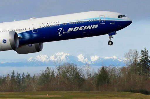 (AP Photo/Ted S. Warren, File). FILE - In this Jan. 25, 2020, file photo a Boeing 777X airplane takes off on its first flight with the Olympic Mountains in the background at Paine Field in Everett, Wash. Boeing Co. reports financial results on Wednesda...