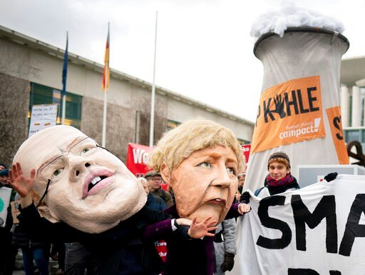(Kay Nietfeld/dpa via AP). Activists depicting German Chancellor Angela Merkel, right, and German Economy Minister Peter Altmaier are protesting in front of the Federal Chancellery against the coal phase-out law and the resulting delayed coal phase-out...